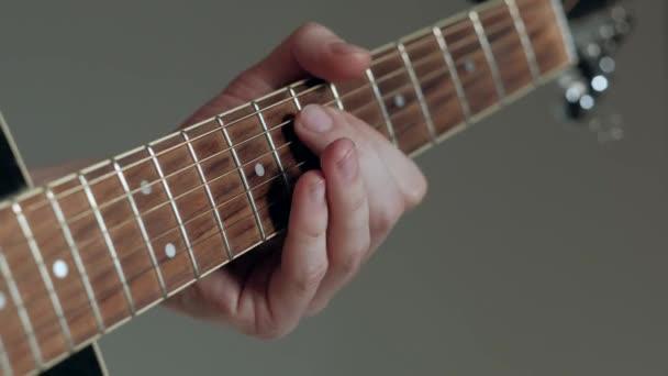 Gitárosa közeli játszik a gitár a fehér háttér előtt. 4k.
