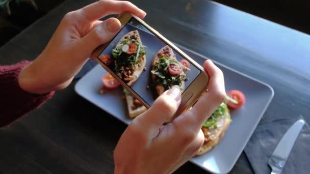 Weibliche Hände fotografieren appetitliche Sefood per Smartphone im Restaurant.