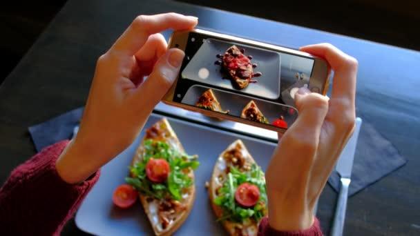 Frauen Hände mit Smartphone nehmen Foto von Essen vor dem Essen in Restaurant