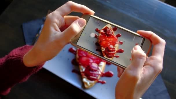 Frauenhände mit Smartphone fotografieren schöne appetitliche Nachspeise.