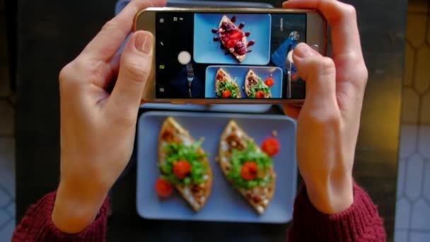 Frauenhände mit Smartphone fotografieren Essen vor dem Essen im Restaurant
