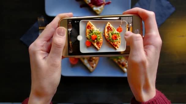 Zenske ruce pomocí Smartphone vzít fotografii z potravin před jíst v restauraci