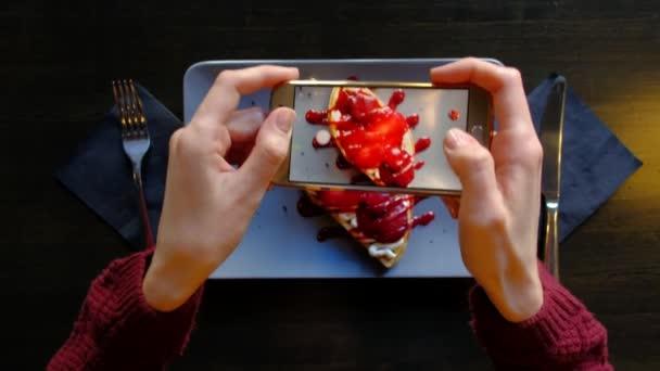 Womans Hände mit Smartphone nehmen Foto von schönen appetitlichen Dessert.