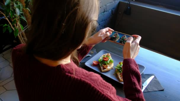 Frau fotografiert appetitliches Essen per Smartphone im Restaurant.