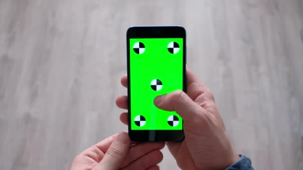Male using smartphone  with green screen in home