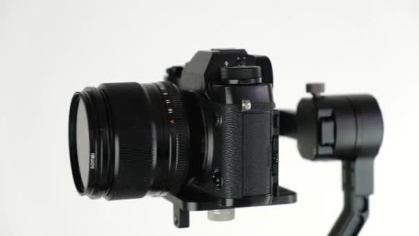 Gimbal s digitálním fotoaparátem se otáčí na bílém pozadí.
