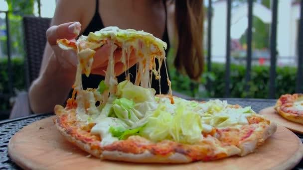 Žena bere lákavý kousek horké pizzy s roztahujíc sýrem.