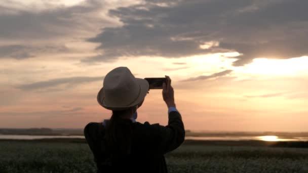 Frauensilhouette fotografiert Sonnenuntergang mit Smartphone.