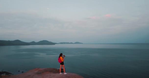 Vrcholy hory, západ slunce moře a mladá žena. Epic na okraji horské údolí s kamením a sluneční záře. 4 k drone letu. Letecká zřizovatel. Evropa Zelená příroda. Film vintage barvy