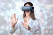 Frau im weißen Hemd tastet mit beiden Händen unsichtbare Objekte in der virtuellen Realität ab und steht mit schwarzer 3D-Brille vor hellem abstrakten Hintergrund. frontales Halblängenporträt
