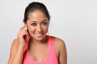Pretty young long-haired brunette woman in pink training top with earbuds, looking at camera and smiling. Close-up bust frontal portrait on white background