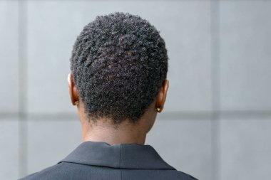 Close up backview portrait of young black woman with short haircut and small earrings, wearing black blazer. Standing outdoors against grey background
