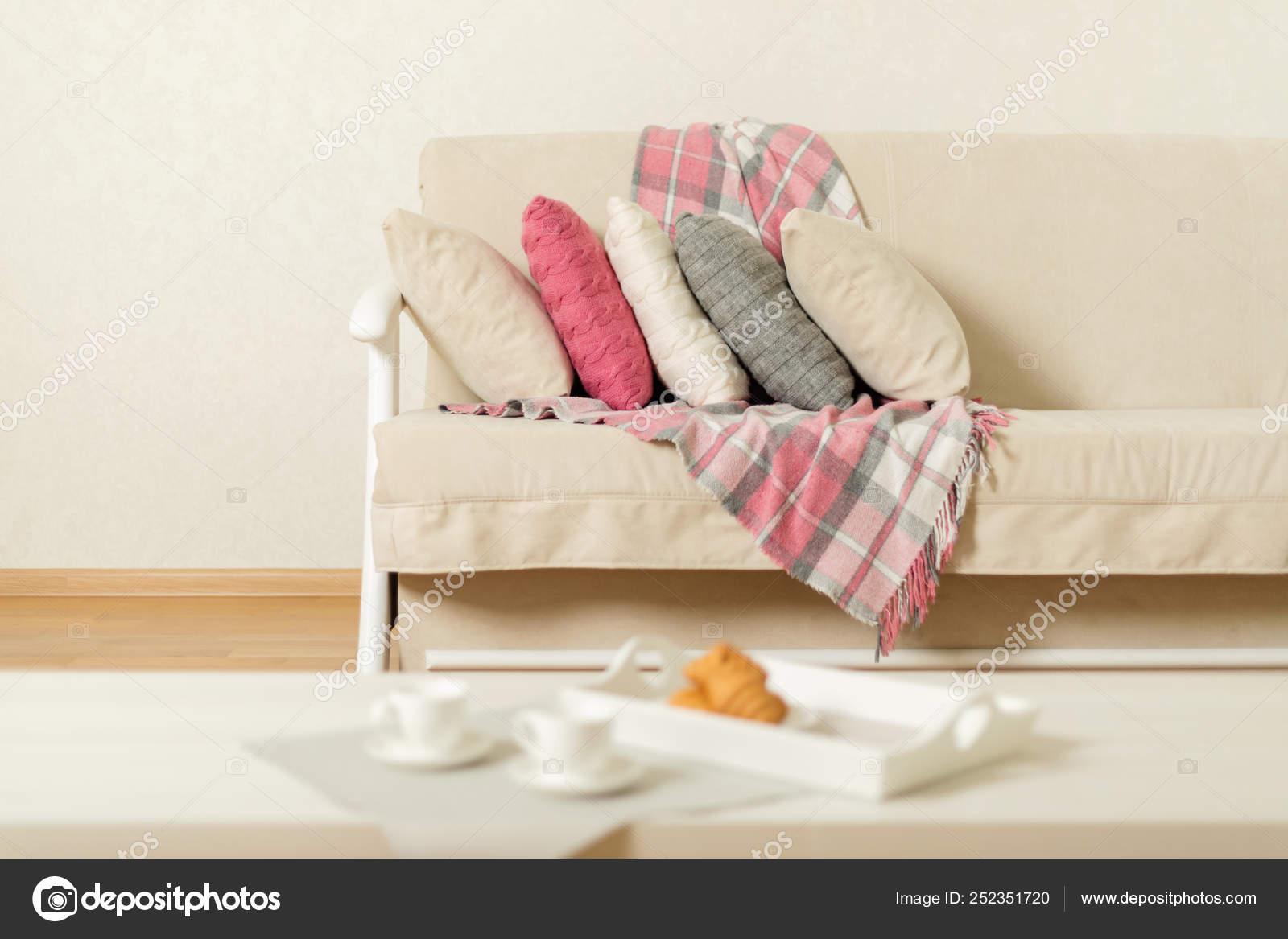 Beige Sofa mit karierten, bunte Kissen (rosa, grau, weiß ...