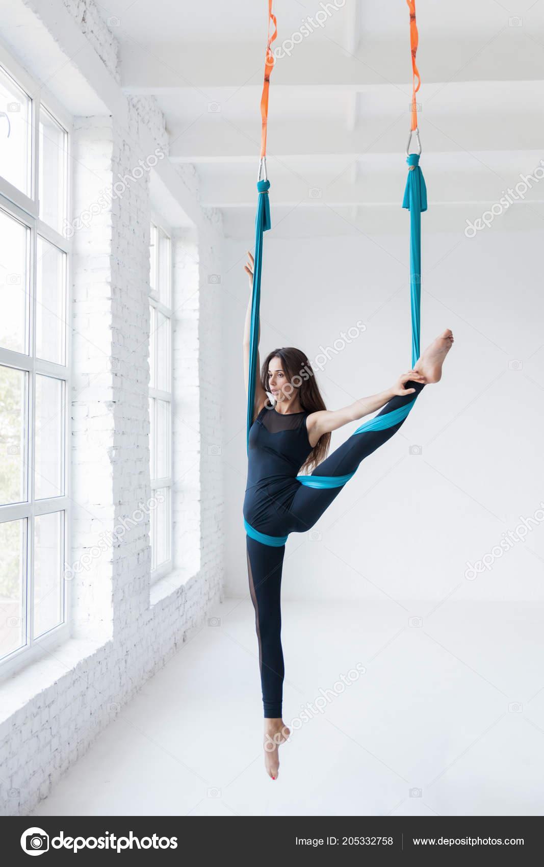 d31cb8975d42 Giovane donna che fa volo yoga esercizi di stretching in palestra bianco —  Foto di ...