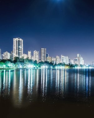 Vertical photo of the Lago Igapo, Londrina - Parana, Brazil. View of the Igapo lake at night and the city, buildings on background. Leisure place, touristic destination of the city.