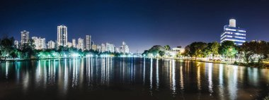 Panoramic photo of the Lago Igapo, Londrina - Parana, Brazil. View of the Igapo lake at night and the city, buildings on background. Leisure place, touristic destination of the city.