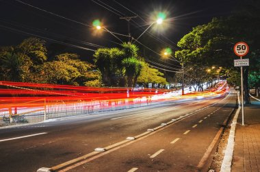Long exposure photo of a street at night with a 50 km/h plate and a warning of electronic fiscalization written in Portuguese. Photo at Higienopolis avenue, Londrina - Parana, Brazil.