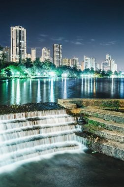 Photo of the Lago Igapo, Londrina - Parana, Brazil. View of the Igapo lake at night, the artificial waterfalls and the city, buildings on background. Leisure place, touristic destination of the city.