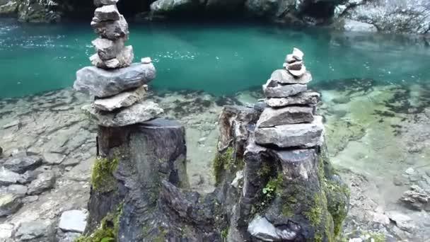 Kameny na břehu horské řeky, na pahýlech oříznutého stromu, vytvářejí atmosféru klidu a feng shui