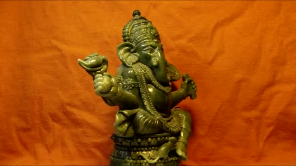 Otáčející se Bůh Ganéša na jasně oranžovém pozadí. V hinduismu Bůh moudrosti a prosperity.