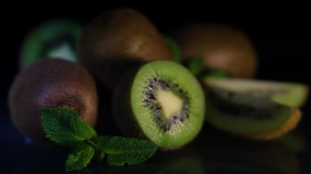 Fruits of juicy beautiful kiwi lie on a table on a black background. Close-up.
