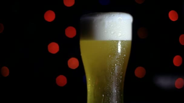 A glass of cold beer on a black background with colored lights is on the bar. Beer is foaming in a glass. HD
