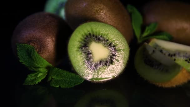 Fruits of juicy kiwi rotate on a table on a black background. Close-up