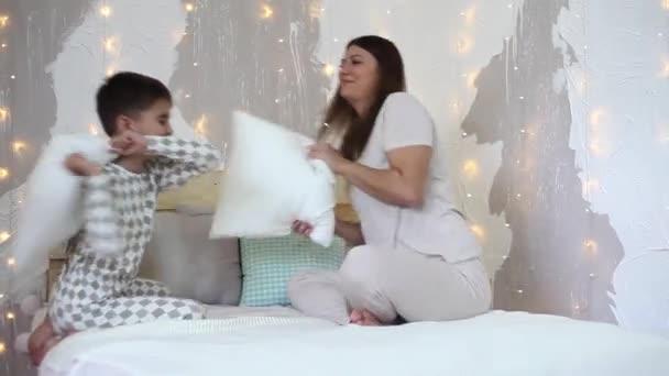 Dívka a chlapec bavit mlátit s pádly, sedí na posteli