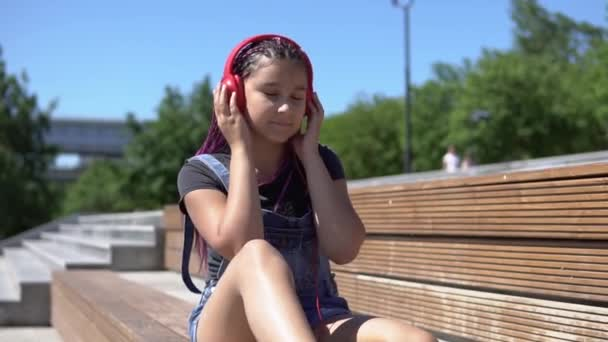 Girl listening to music on headphones sitting on a bench in summer park. slow motion