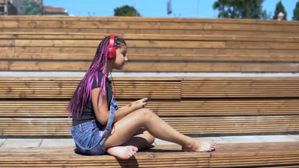 Girl listening to music on headphones using smartphone sitting on a bench with a good mood in summer park. slow motion. Overall plan