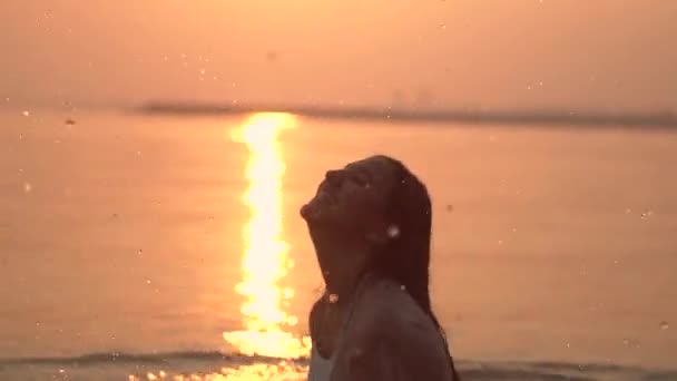 Happy girl with dark hair doing splashing hands standing in the river against the sun during sunset. slow motion. Close-up. HD. Happy day