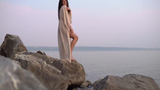 Szexi lány modell áll szemben a tenger, egy hosszú ruha kövek. lassú mozgás. 4k
