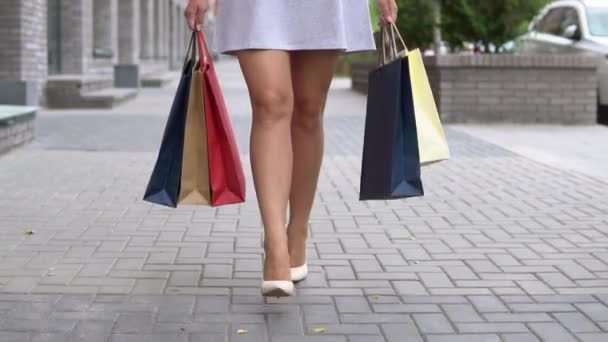Ta holka nese balíčky různých barev s nákupy po nakupování na ulici. Zpomalený pohyb. HD