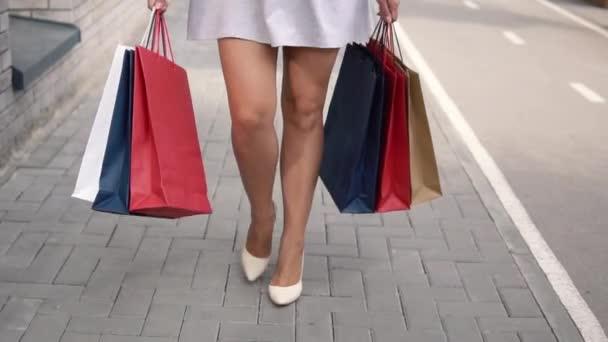 Ta holka nese balíčky s nákupy v rukou po nakupování. Zpomalený pohyb.