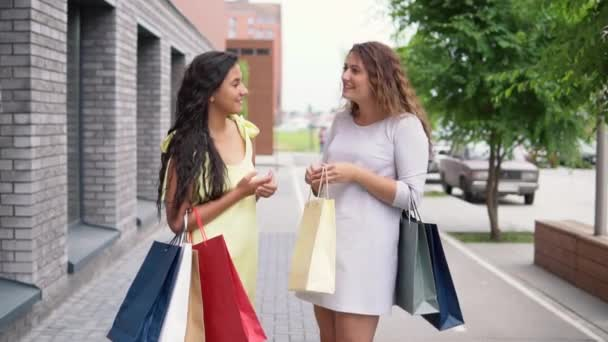 Two girl friends discuss shopping after shopping. slow motion.