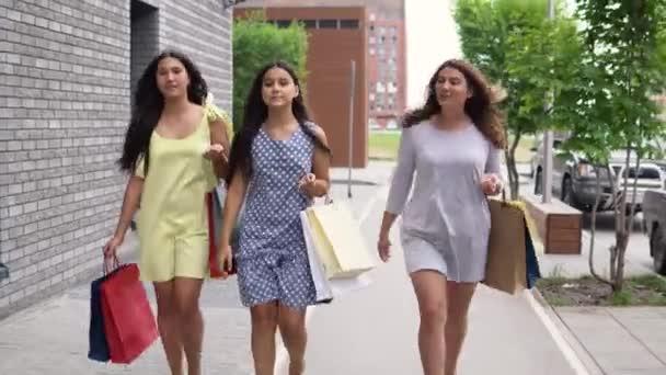 9501e45491 Tres hermosas chicas caminan por la calle después de ir de compras. 4k–  metraje de stock