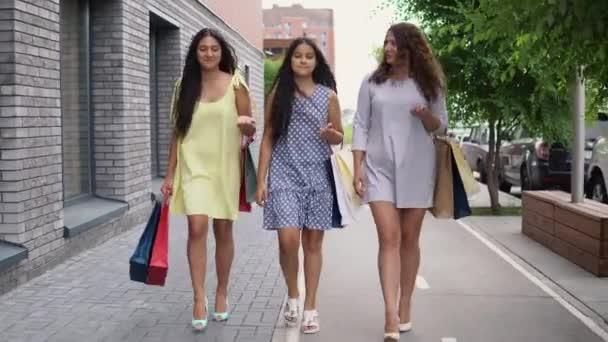 95339101c8 Tres hermosas chicas a pie por la calle con bolsas en sus manos después de  ir de compras, tener buen humor. 4k– metraje de stock