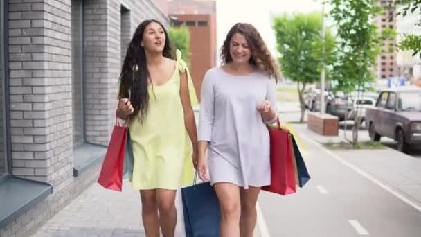 262887b492 Dos hermosas chicas caminan por la calle con los paquetes en sus manos  después de ir de compras, tener buen humor. 4k– metraje de stock