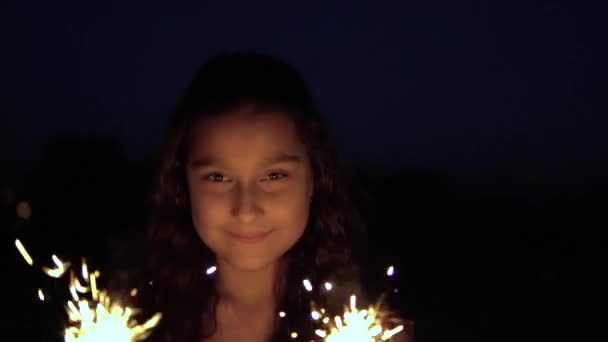 A young woman with long dark hair holds fireworks at night in the background of the city and is happy to have a good mood. slow motion. Portrait. HD