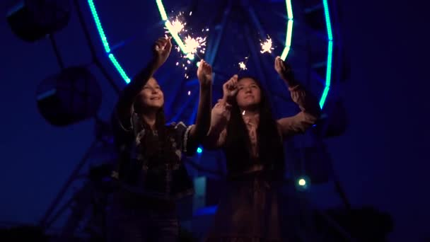 Two girls with fireworks in their hands on the background of a Ferris wheel. slow motion.