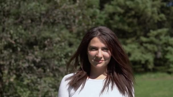 Attractive girl posing in the park in sunny weather. slow motion.HD