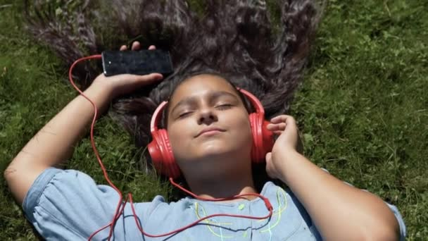 Attractive girl with long hair lies on the grass in the park and listens to music in red headphones using a smartphone.slow motion. HD