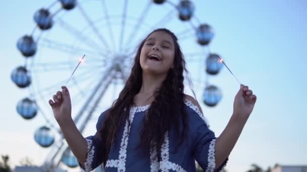 The girl holds fireworks in her hands and rejoices standing on the background of the ferris wheel. slow motion.