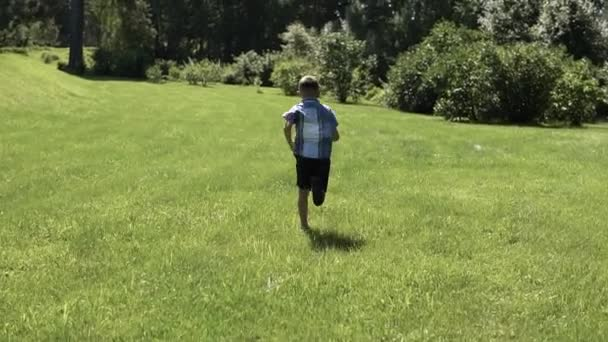 attractive boy runs along the grass in the park having a good mood. slow motion