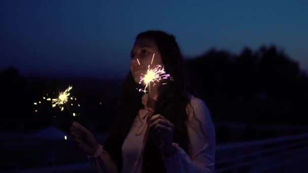 Young girl in a dress with long hair stands with fireworks in the hands on a background of a night city having a good mood. slow motion. Portrait