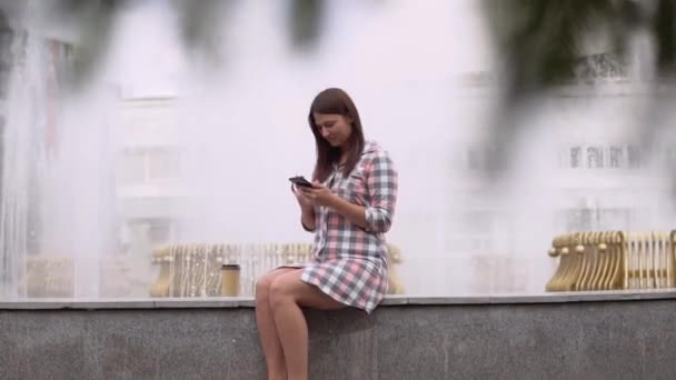 A girl in a dress sits near a fountain in the park and uses a smartphone. slow motion. HD