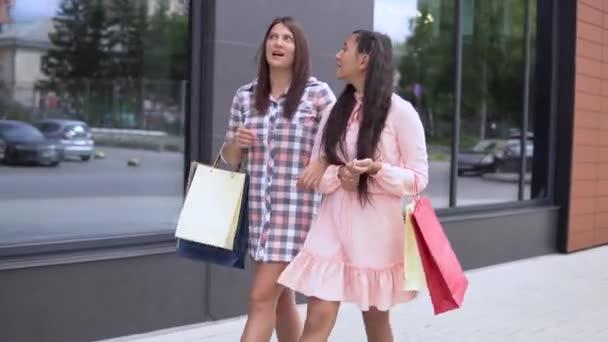 Dvě dívky jít po nakupování a provádět nákupy v balíčcích. 4k