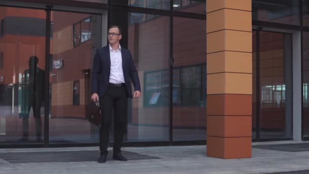 Mladý atraktivní podnikatel v brýlích tancuje nedaleko obchodního centra v ruce držel kufřík. HD. Zpomalený pohyb