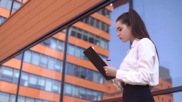 Obchodní dívka s tmavými vlasy dělá poznámky v pracovních dokumentech stojící nedaleko obchodního centra. 4k