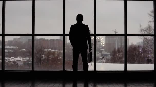 businessman looks time on wrist watch in office near window